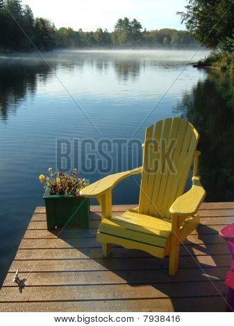 Silla de Muskoka amarillo en el muelle en el lago