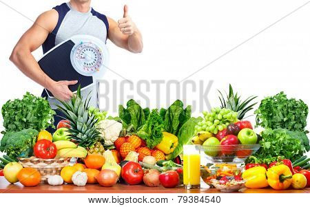 Man with scales fruits and vegetables background