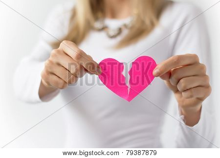 Woman symbolically tearing up paper heart