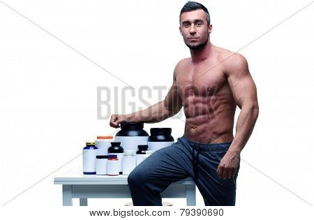Handsome muscular man leaning on the table with sports nutrition