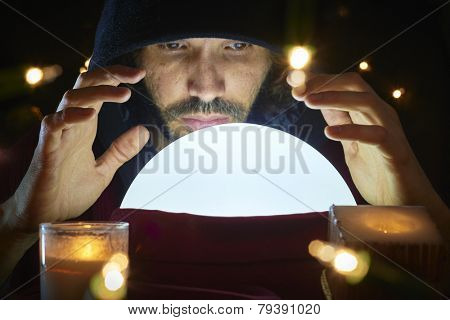 Very low key portrait of hooded man reading fortune on bright crystal ball, surrounded by candle light.