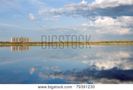 Corn Silo Across A Lake With Reflection And Flamingo In The Water