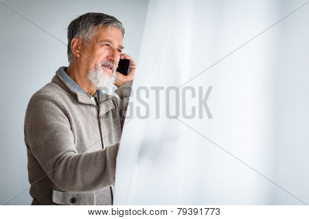 Handsome senior man calling on his cell phone and looking from a window at his house (shallow DOF; color toned image)