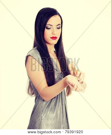 Beautiful woman applying perfume on her body, bright red perfume bottle