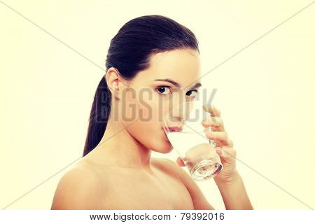 Beautiful young woman drinks clear mineral water from glass