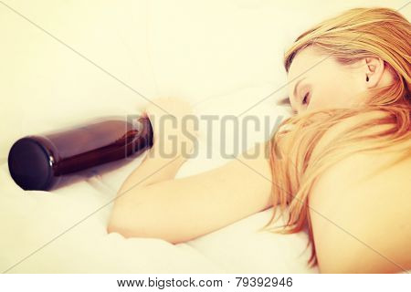 Drunk zoung topless woman sleeping on bed with bottle of vine in hand. Isolated on white