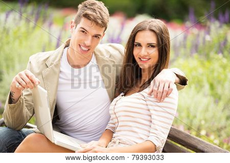 Young Couple In A Park With Laptop