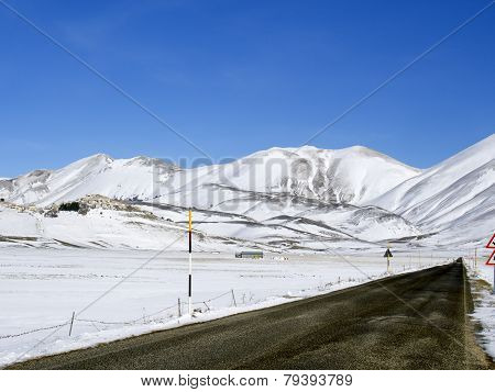 Asphalt Straight Road Along  Plateau Of Castelluccio Of Norcia In Winter,
