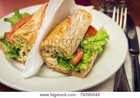 Table set with a sandwich with cheese, lettuce and tomato