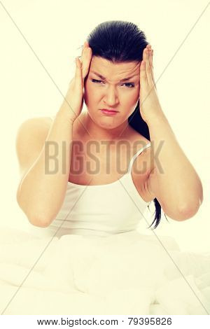 Young caucasian female sitting on bed. She have terrible headache, illness or hangover.