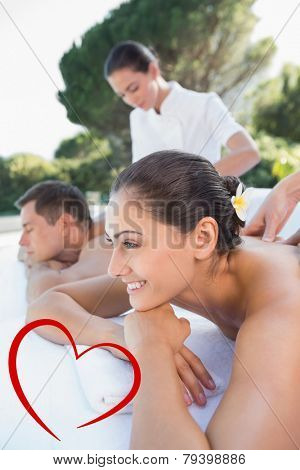 Attractive couple enjoying couples massage poolside against heart