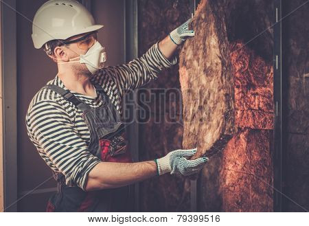 Builder in protective wear applying material on a wall