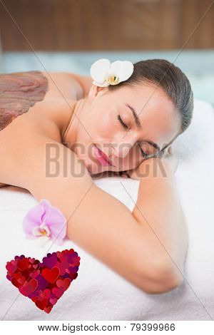 Attractive woman receiving chocolate back mask at spa center against heart