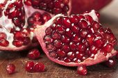 stock photo of pomegranate  - Pomegranate sitting on a dark brown wooden cutting board - JPG
