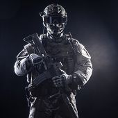 stock photo of rifle  - Special forces soldier with rifle on dark background - JPG