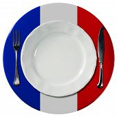 foto of plating  - Concept of French cuisine with white plate and under plate colored with the colors of French flag and silver cutlery isolated on white background - JPG