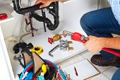 foto of plumber  - Plumber with Plumbing tools on the kitchen - JPG