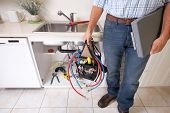 stock photo of plumber  - Plumber on the kitchen - JPG