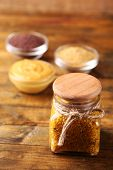 picture of mustard seeds  - Dijon Mustard in glass jar  and mustard seeds and sauce in bowls on wooden background - JPG