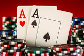 picture of ace spades  - Stack of chips and two aces on the table on the red baize  - JPG