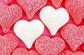 pic of shapes  - Two white heart shaped Valentines Day candies with red background - JPG