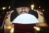 stock photo of fortune-teller  - Very low key portrait of hooded man with eyes covered reading fortune on bright crystal ball - JPG