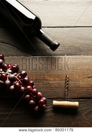 Glass bottle of wine with corkscrew and grapes on wooden table background