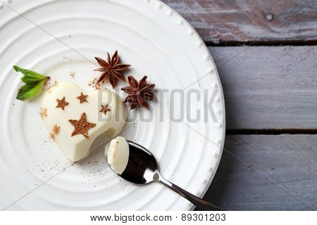 Tasty panna cotta dessert on plate, on wooden table
