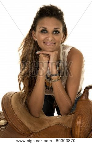 Cowgirl Hands Under Chin Smiling Leaning On Saddle