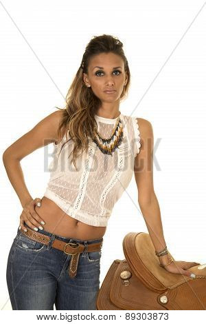 Cowgirl In A White Top Leaning On A Saddle