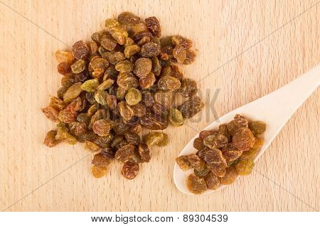 Heap Of Raisins And Wooden Spoon On Board