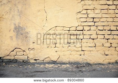 Yellow Damaged Brick Wall And Asphalt