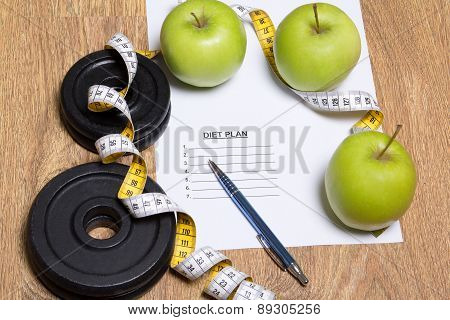 Diet Plan Concept - Apples, Measure Tape And Dumbbell