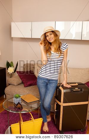 Pretty young woman posing with suitcase on holiday, smiling.