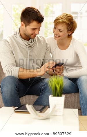 Happy couple sitting on sofa at home, using mobilephone, smiling.