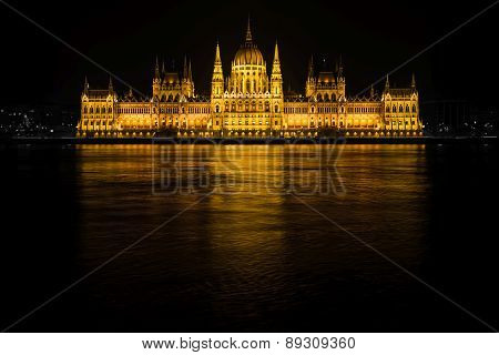 The Parliament Of Budapest And Its Reflection In The Long Exposed River At Night From The Other Side