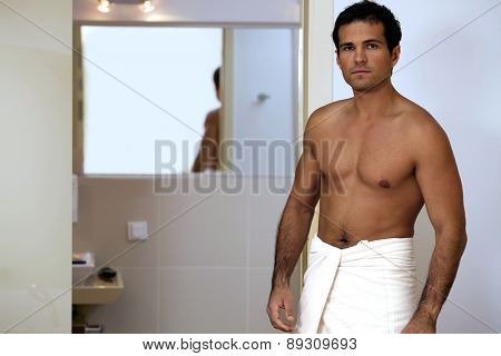 Portrait of young man wrapped in towel