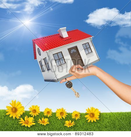 House and key in womans hand with flowers