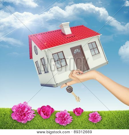 House and key in womans hand with pink flowers