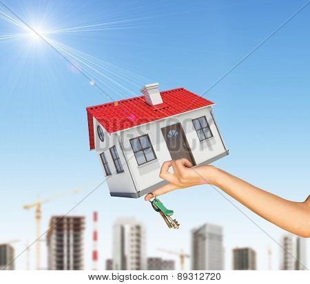 House and keys in womans left hand with cityscape