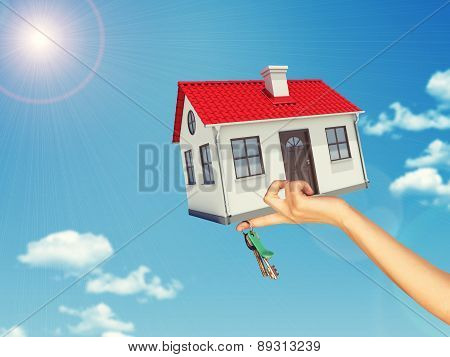 House and keys in womans left hand
