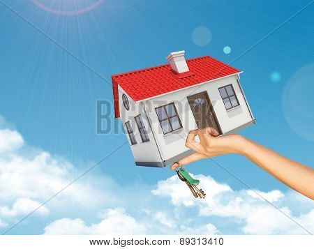 House and keys in womans left hand under clouds