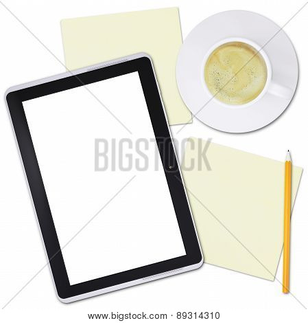 Black tablet and cup of coffee on plate, top view