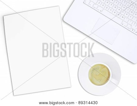 White laptop with paper and coffee cup, top view