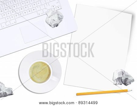 White laptop and crumpled paper with pencil