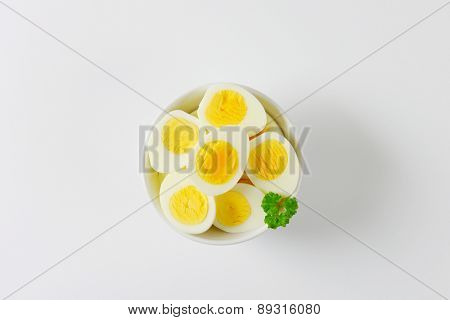 overhead view of halved hard boiled eggs in the bowl with piece of parsley