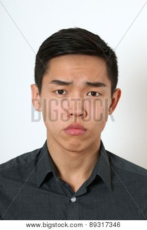 Strict young Asian man looking at camera.