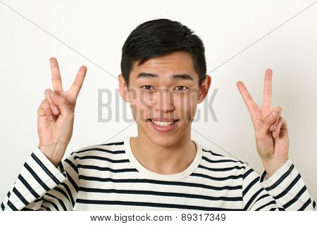 Smiling young Asian man giving two victory signs and looking at camera.