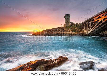 Calafuria Tower Landmark On Cliff Rock, Aurelia Bridge And Sea On Sunset. Tuscany, Italy.
