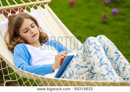 Girl reading a book in a hammock in the garden
